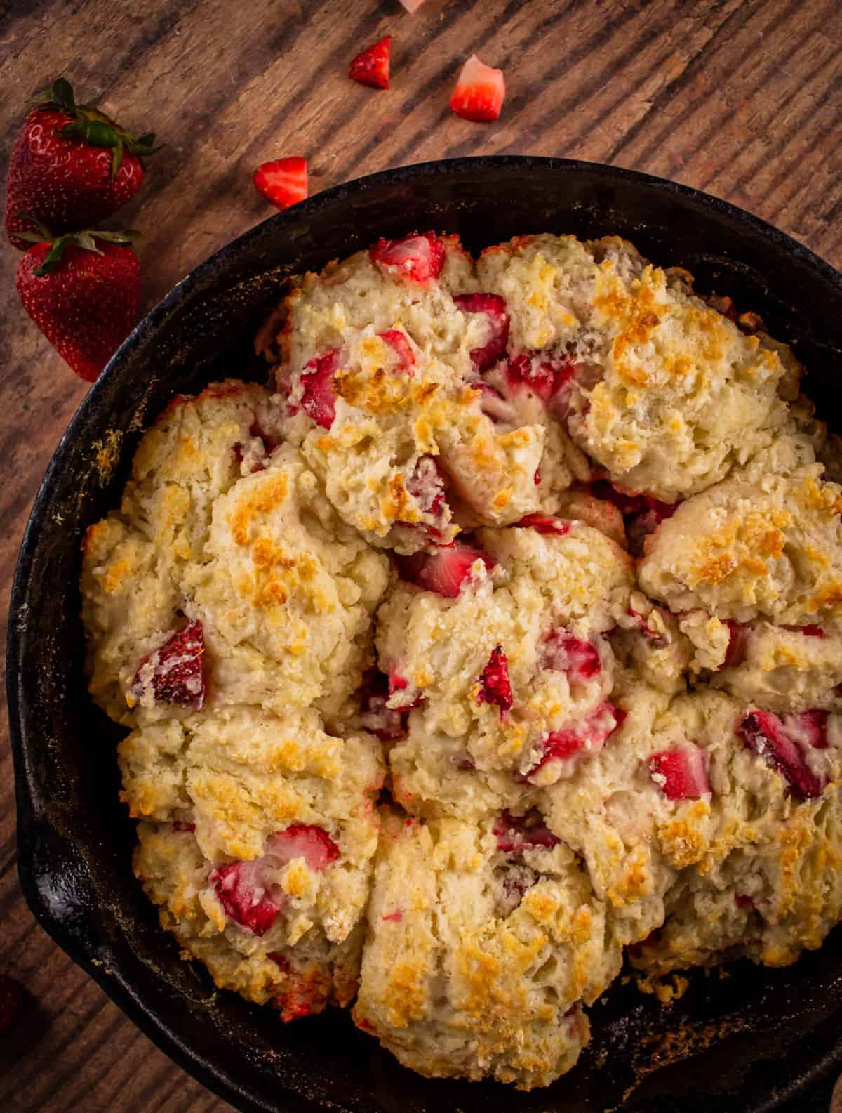 freshly baked biscuits with strawberries in a cast iron skillet