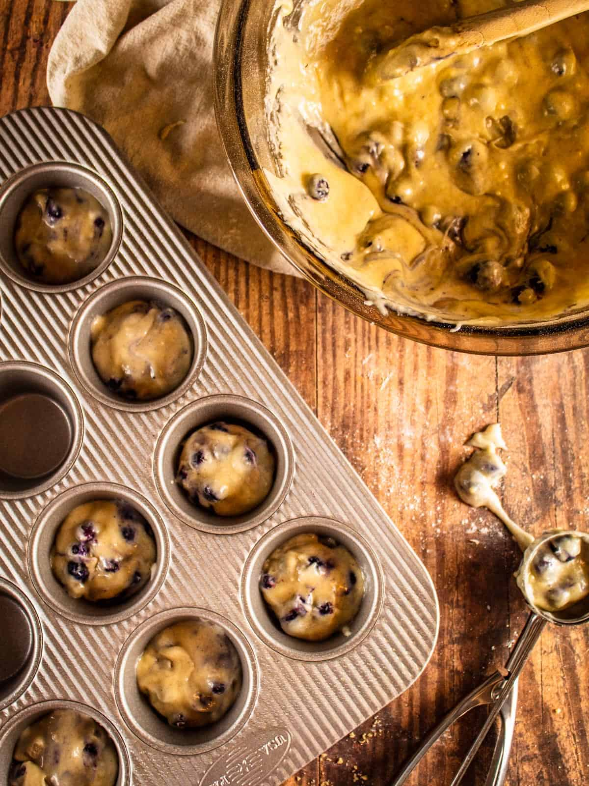 muffin tin with blueberry muffin batter in it