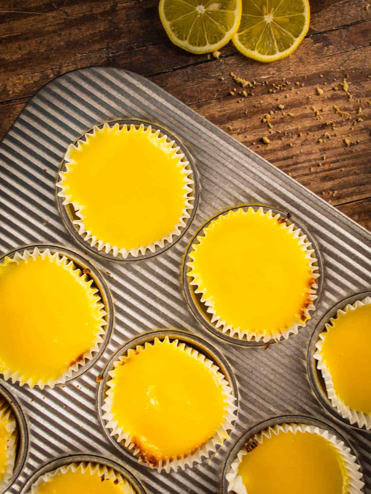 mini cheesecakes topped with lemon curd in a muffin pan