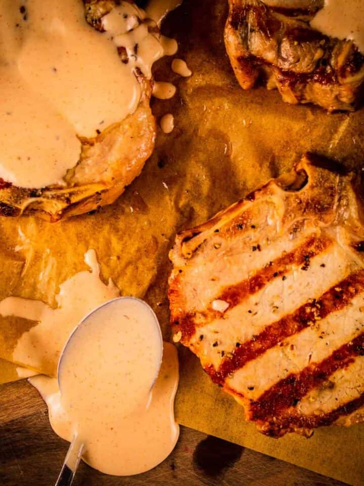 three grilled pork chops with two of them covered in white bbq sauce