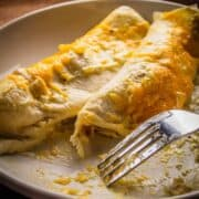 two white enchiladas on a plate with a fork