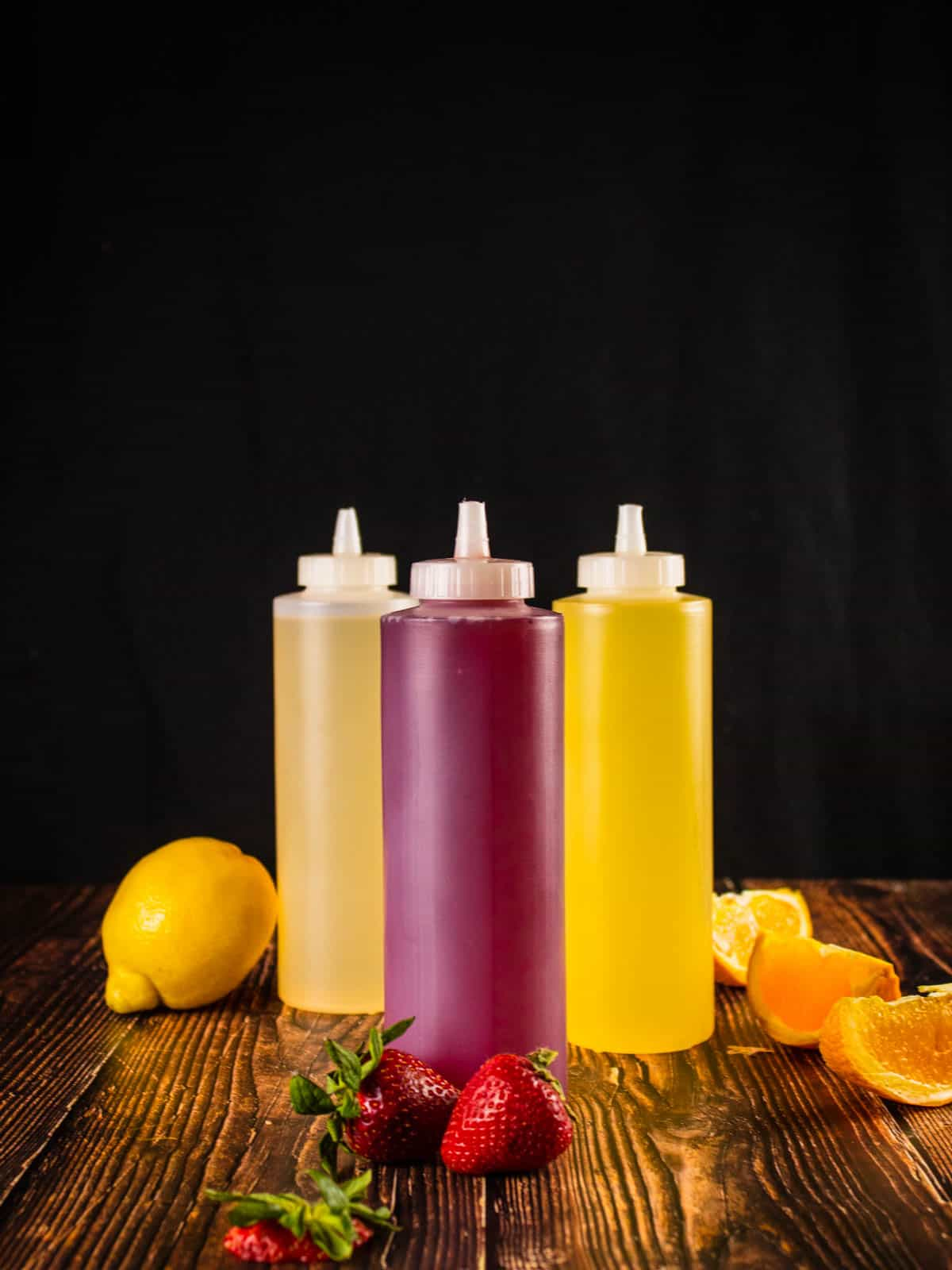 red, yellow and orange simple syrups in a squeeze bottles next to fresh fruit
