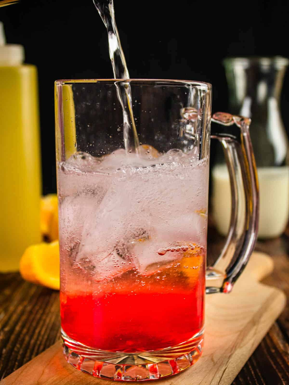 club soda pouring into a clear glass mug with ice and strawberry simple syrup