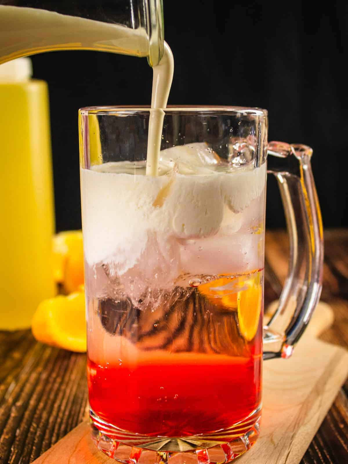 cream pouring into a glass with strawberry simple syrup and club soda