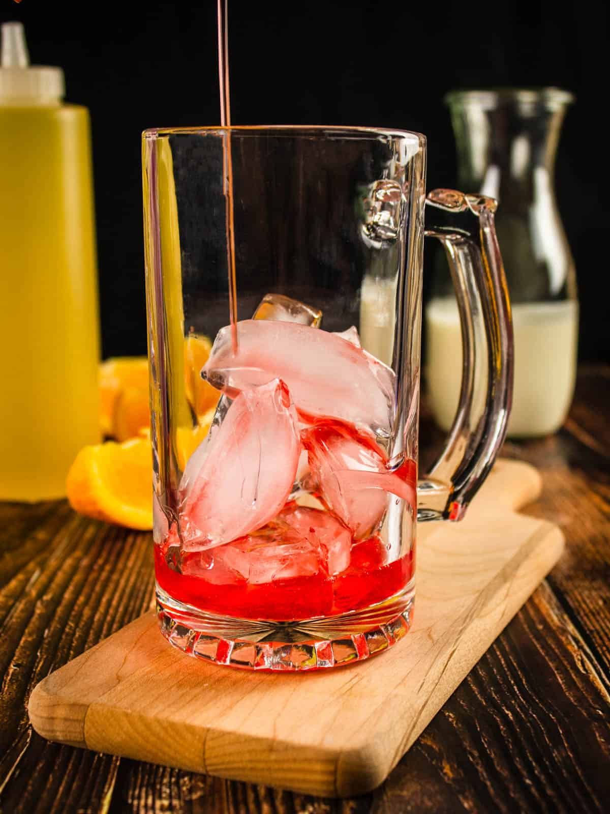 red simple syrup pouring into a glass mug with ice