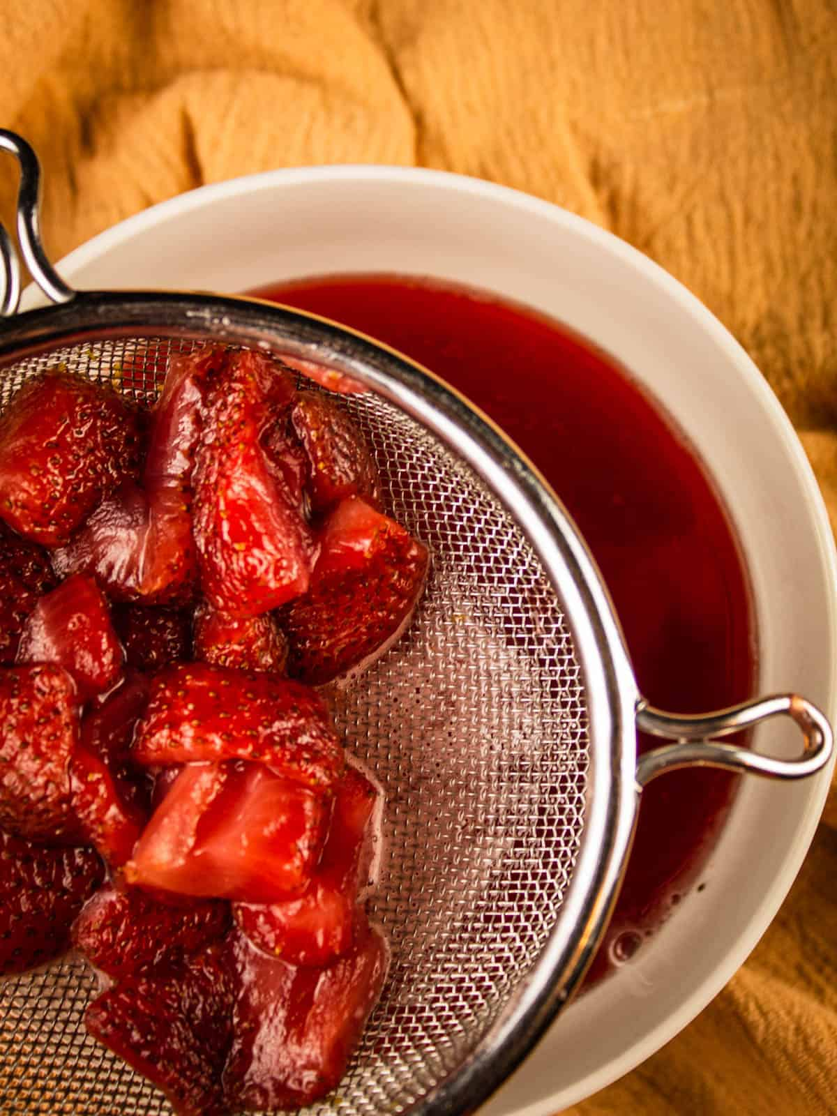 strainer filled with strawberries over a white bowl of red liquid
