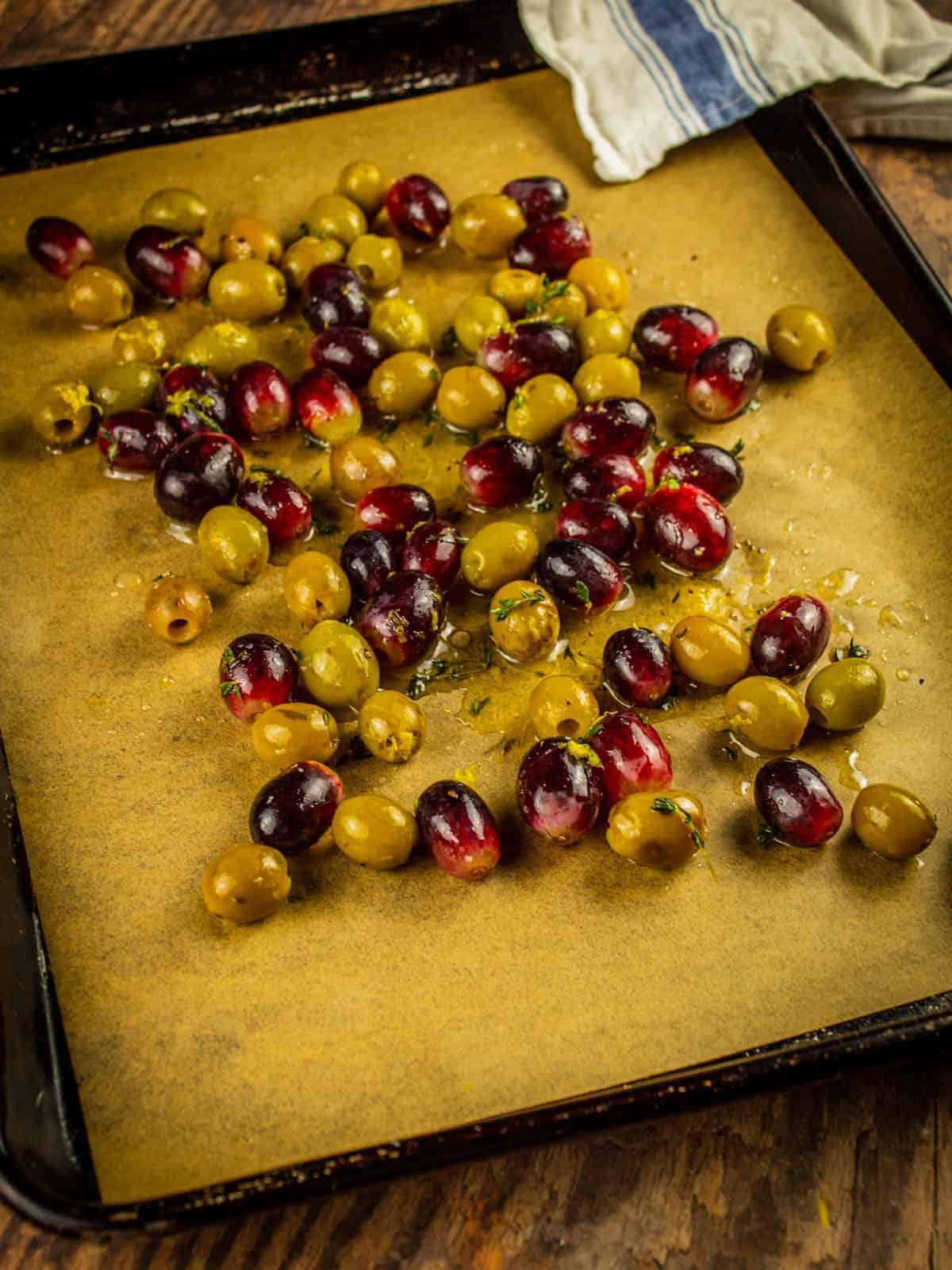 seasoned red grapes and green olives on a sheet pan