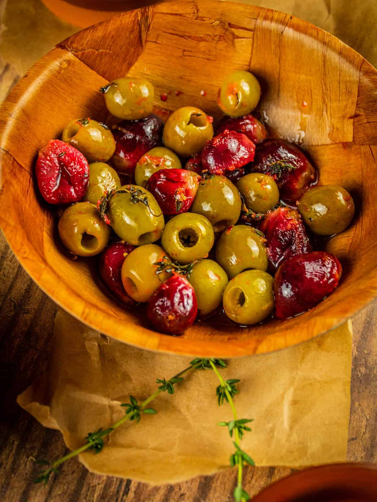 wooden bowl of red roasted grapes and green roasted olives