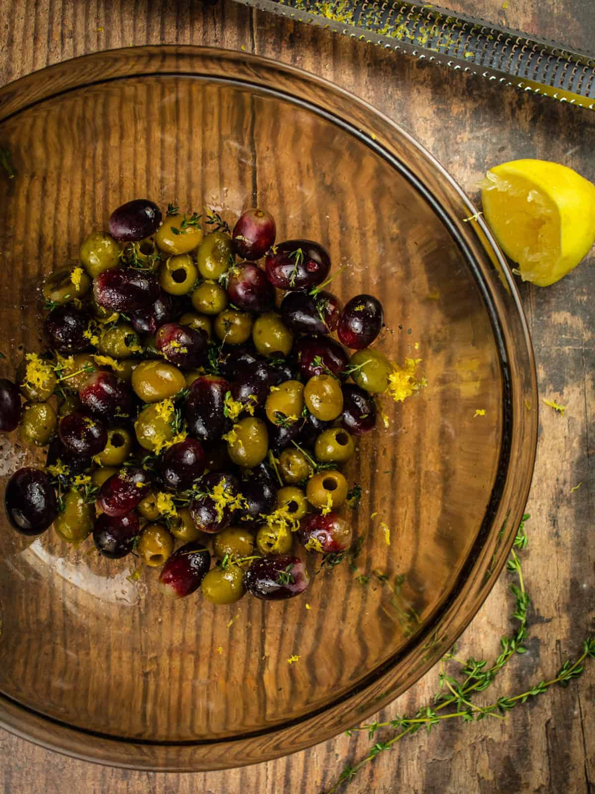 grapes, olives, lemon zest, thyme and olive oil in a bowl