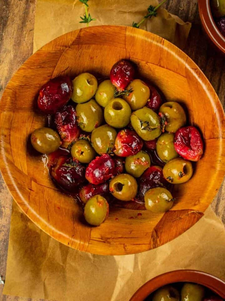 wooden bowl with roasted green olives and purple grapes