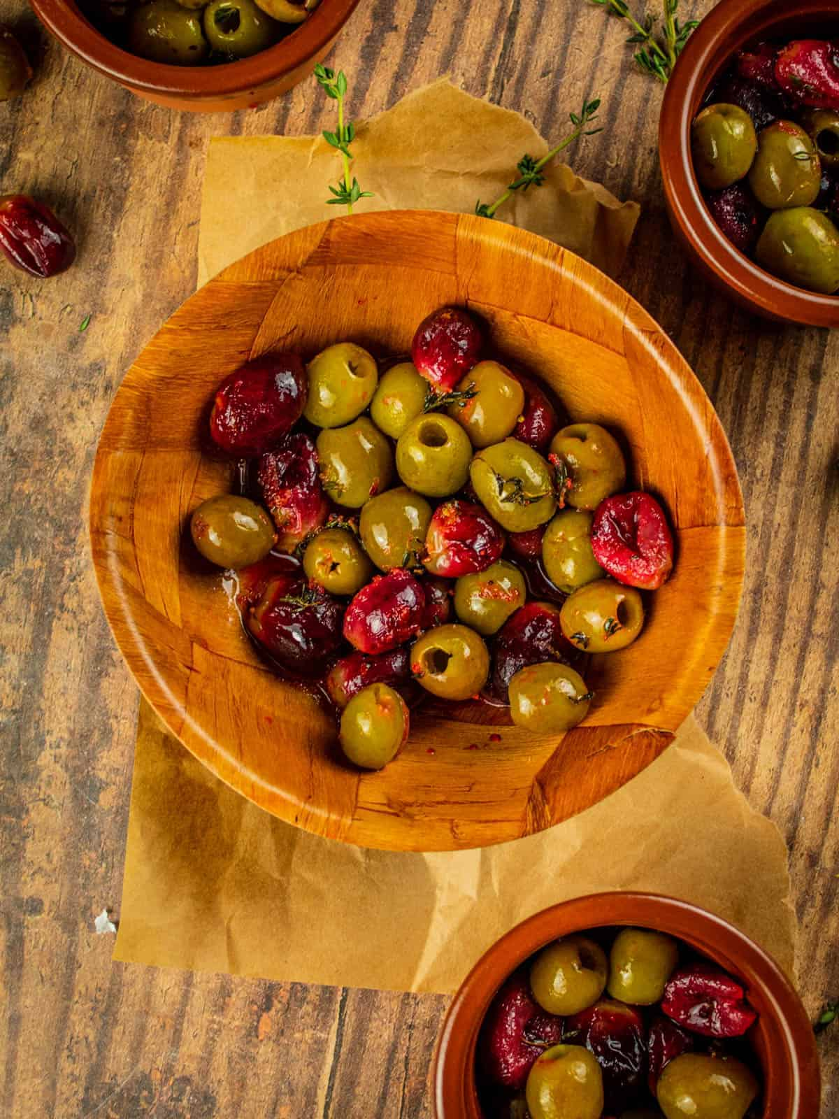small brown dishes with red grapes and green olives that have been roasted
