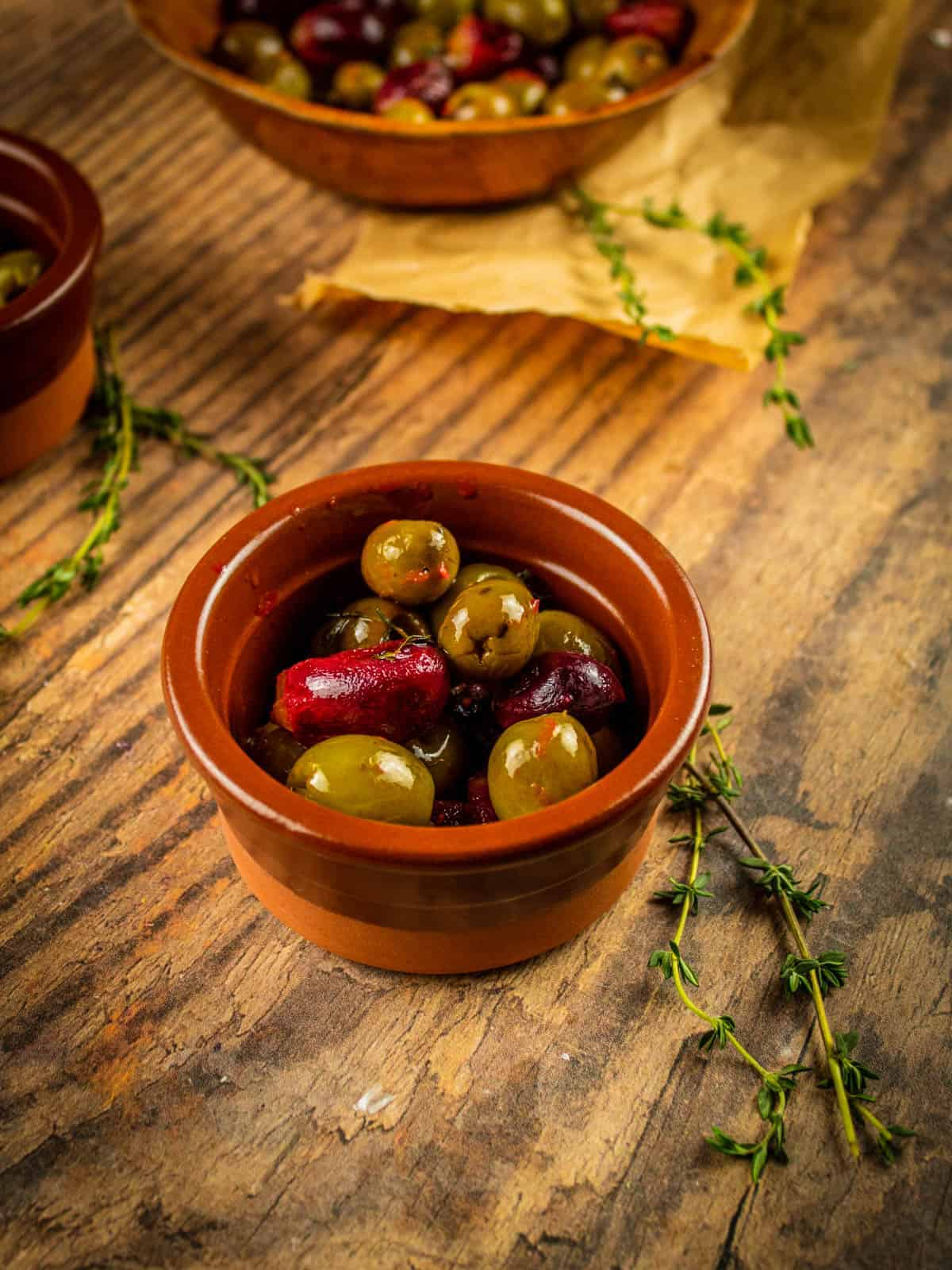 brown ceramic dish of roasted olives and grapes with a thyme sprig