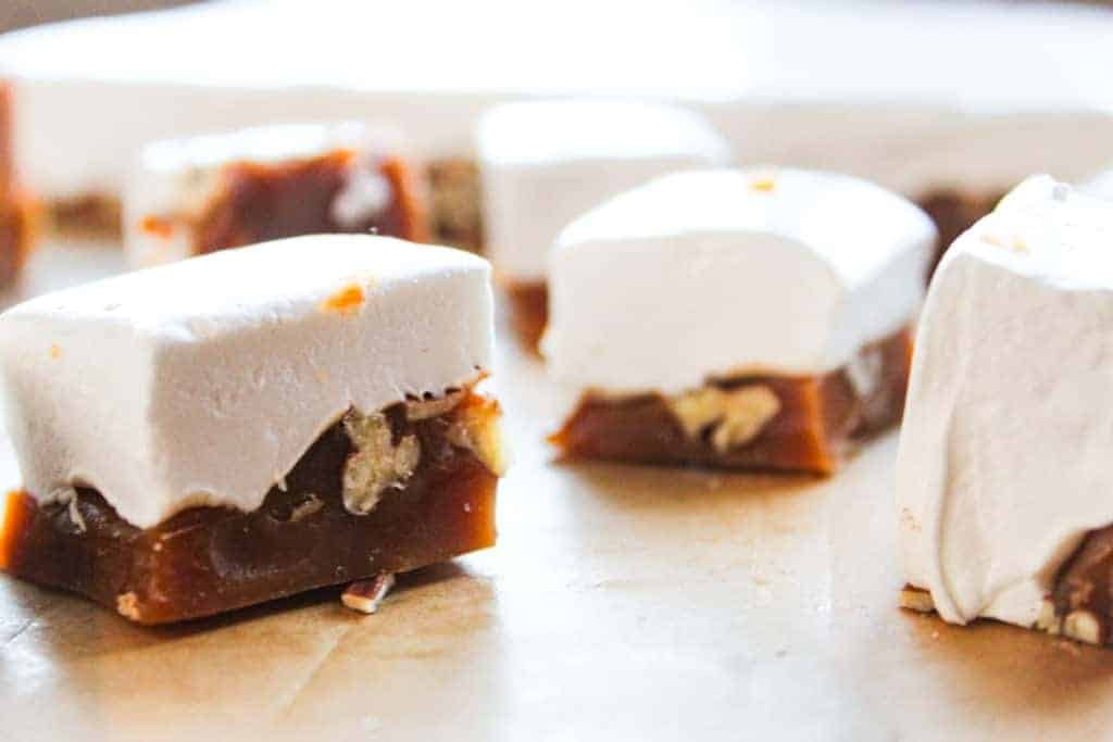 pieces of homemade marshmallow candy with caramel and pecan pieces