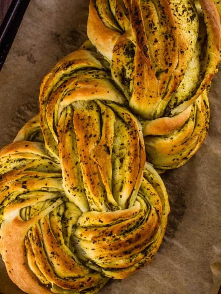 braided italian bread with pesto on a sheet pan