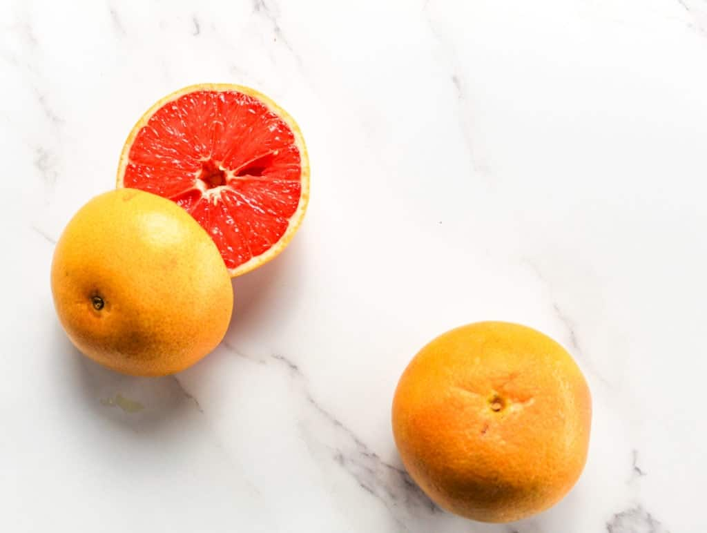 sliced grapefruit on a white marble countertop