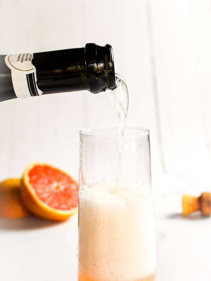 bottle pouring prosecco into a glass for grapefruit elderflower cocktail with grapefruit and cork in the background