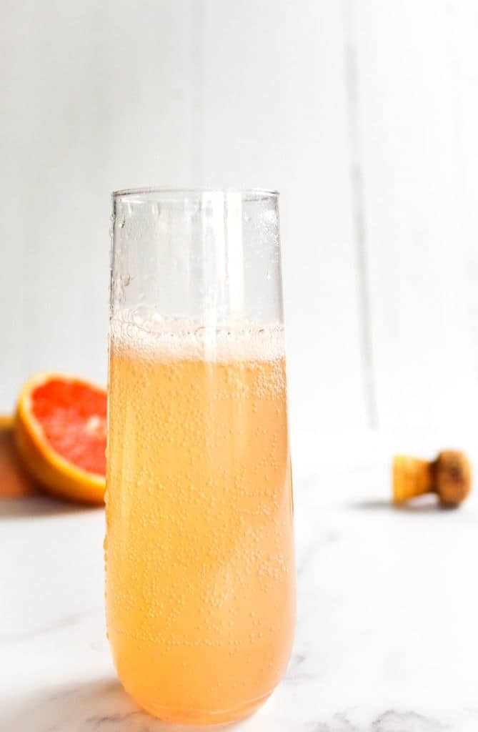 Grapefruit Elderflower Cocktail in a champagne glass with champagne cork and grapefruit in the background