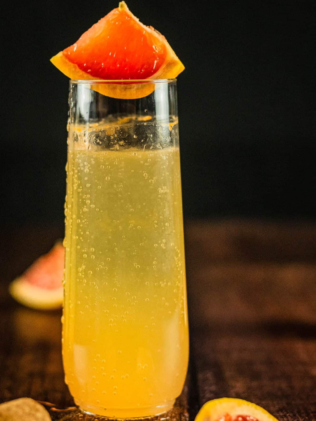 champagne glass with grapefruit cocktail and wedge of grapefruit
