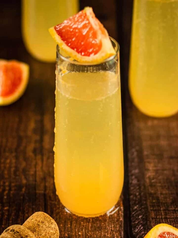 champagne flute with grapefruit cocktail topped with wedge of grapefruit