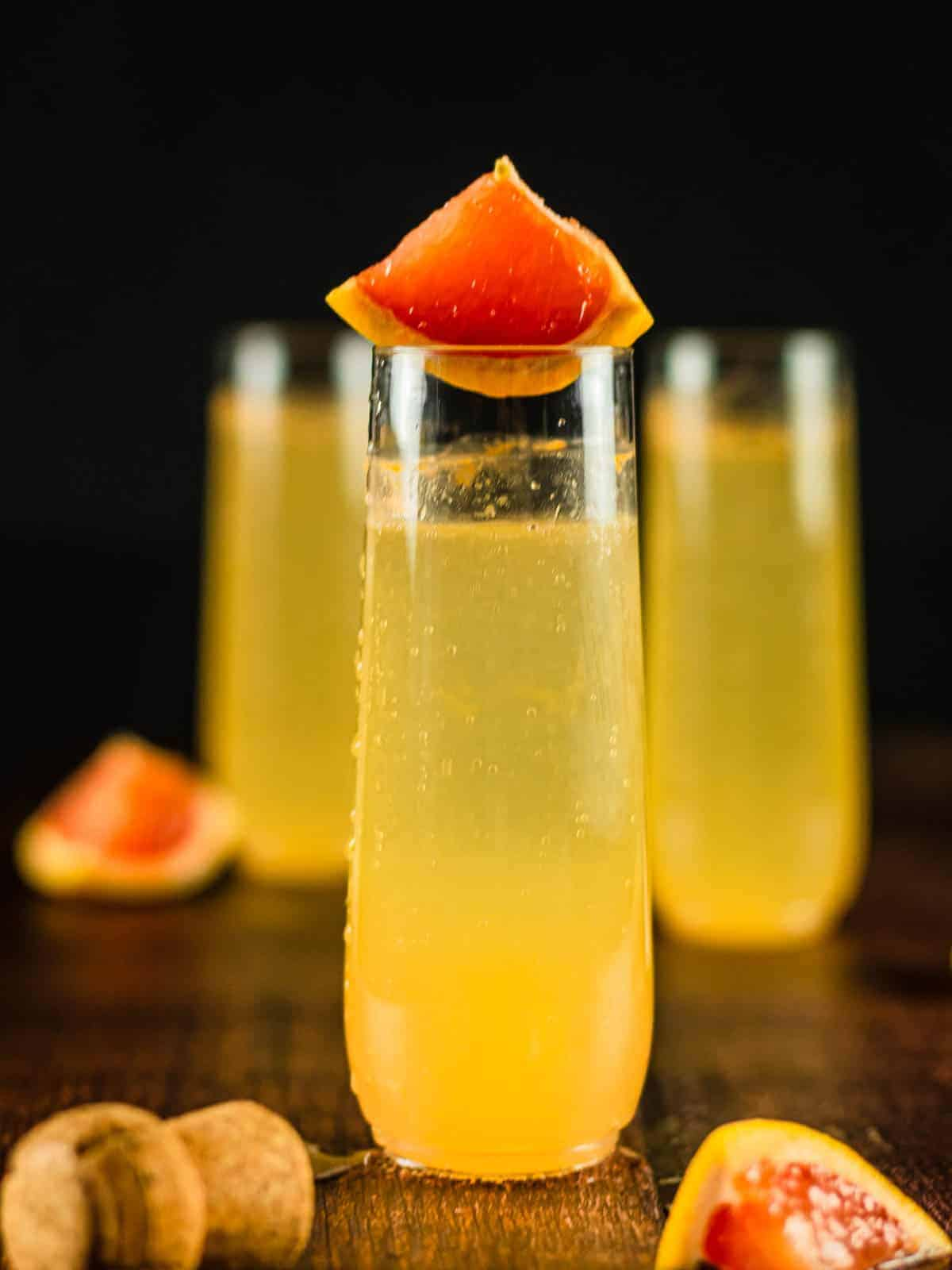 three glasses with cocktail made with grapefruit juice
