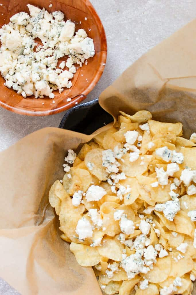 kettle chips with crumbled blue cheese on top and a bowl of crumbled blue cheese next to it