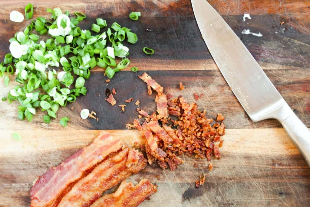 cutting board with knife and sliced scallions and bacon that has been chopped