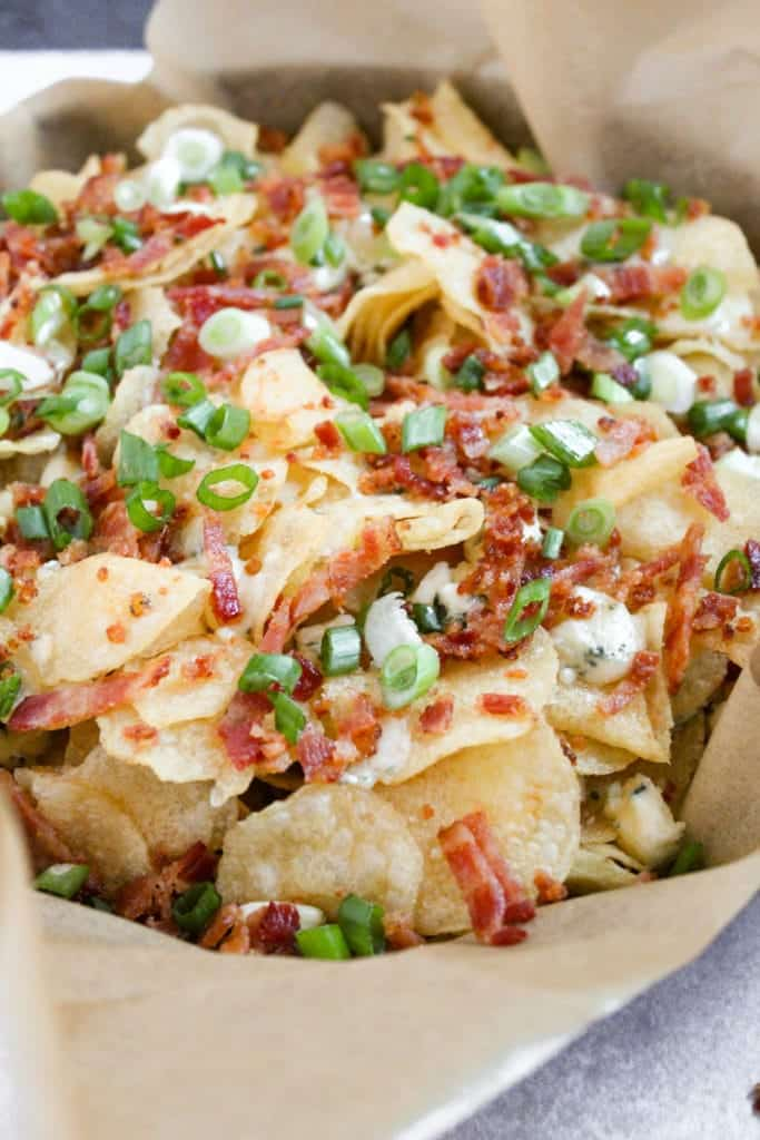 pan of chips with crumbled bacon, sliced green onions and blue cheese