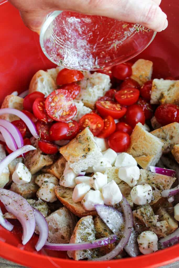 hand pouring a dish of dressing onto panzanella
