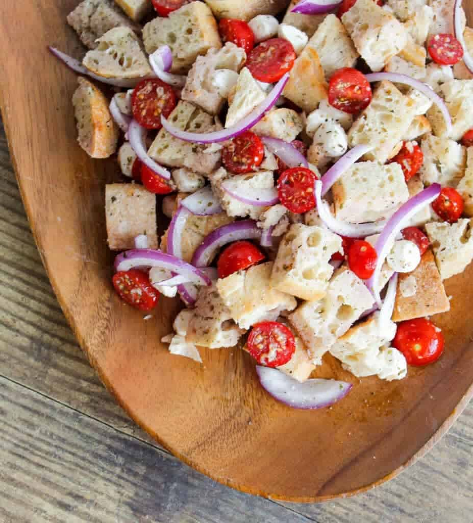 simple summer panzanella salad with tomatoes, bread, cheese and onions on a serving platter