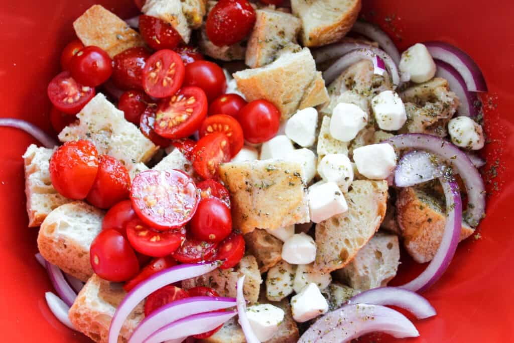 mozzarella cheese, cut grape tomatoes, sliced red onion and cubed sourdough bread in a bowl