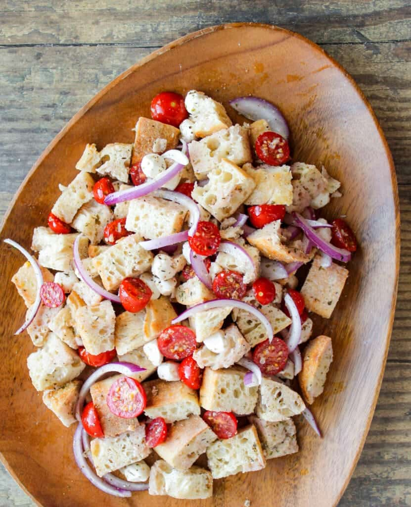 large wooden serving platter with panzanella salad