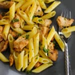 gray plate with silver fork with gluten free penne with pieces of lemon chicken and fresh parsley