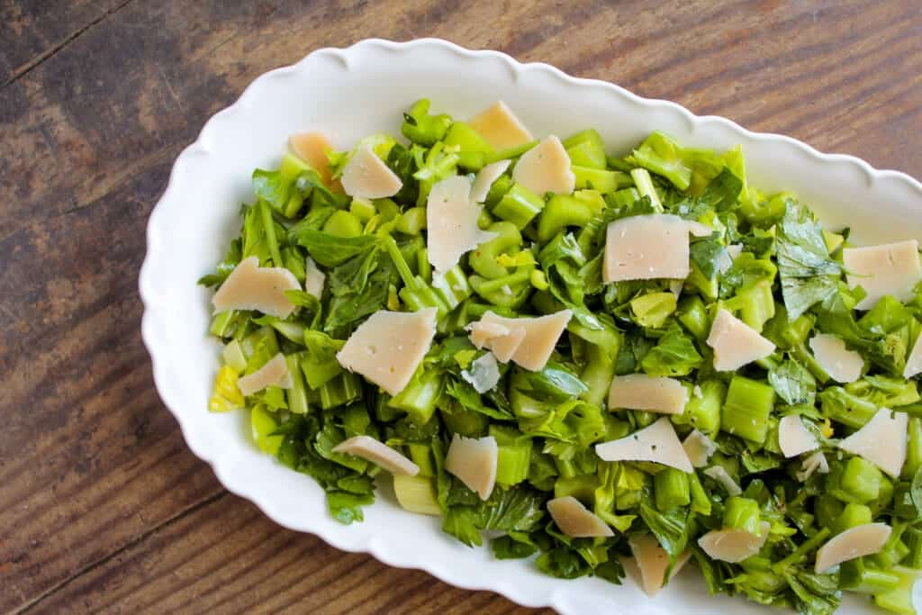 serving platter of celery salad with parmesan cheese on a wooden table