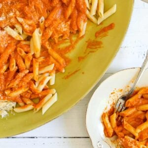 green platter with pasta and red orange sauce with cheese and spoon