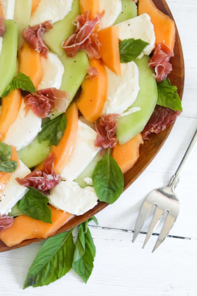 platter with sliced mozzarella, honeydew, cantaloupe, fresh basil and proscuitto with serving fork