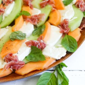 melon and prosciutto caprese salad with lemon vinaigrette and fresh basil leaves on a wooden platter