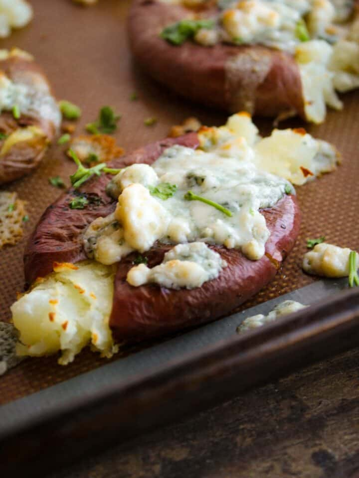 close up shot of roasted smashed red potato that is sprinkled with blue cheese and fresh parsley