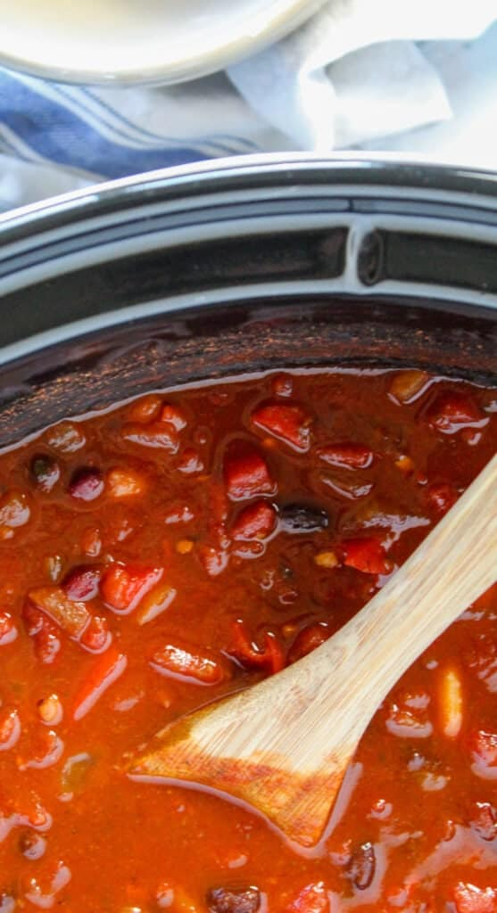 close up shot of a wooden spoon in chili in the slow cooker with a bowl and striped towel in the background