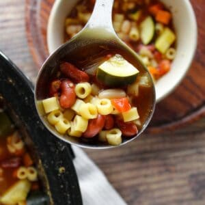 ladle filled with minestrone soup with a white bowl of soup and crockpot full of soup in the background
