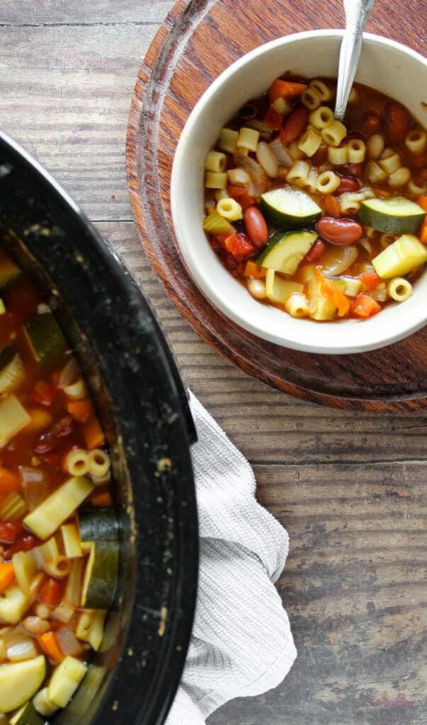 slow cooker and serving bowl with spoon, both next to each other and filled with minestrone