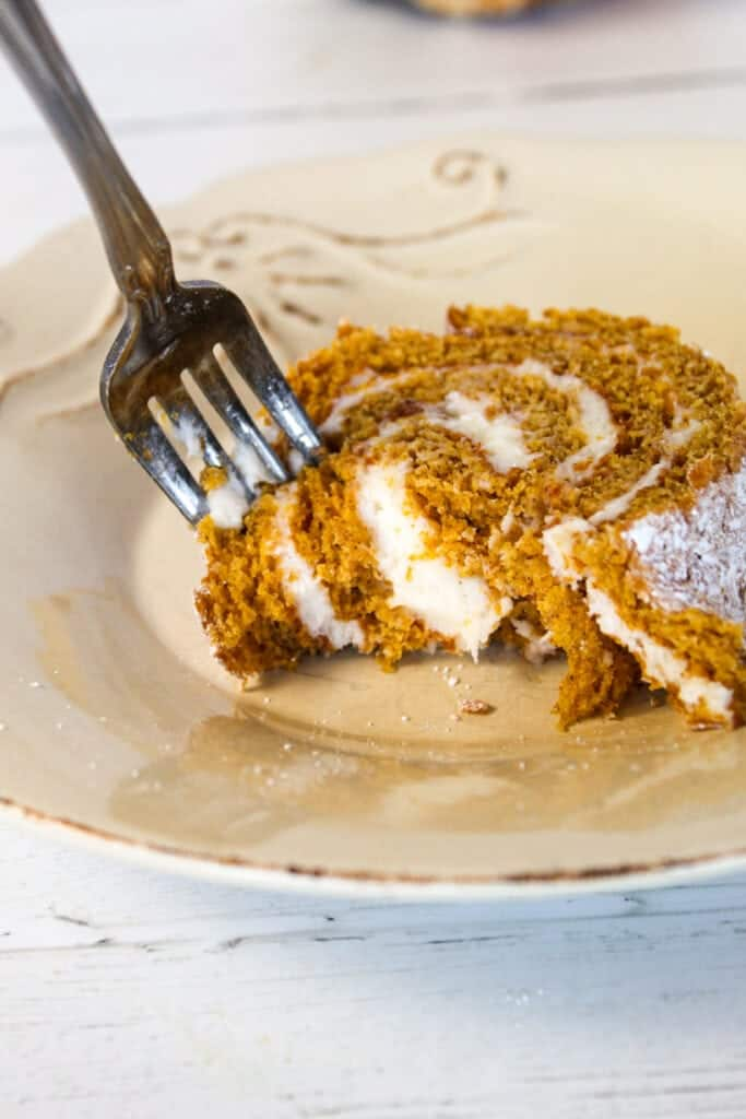 fork stuck in a sliced of pumpkin roll with a bite taken from it