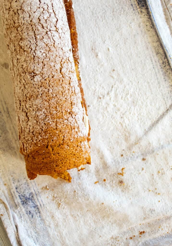 pumpkin cake rolled up on a towel with powdered sugar on it