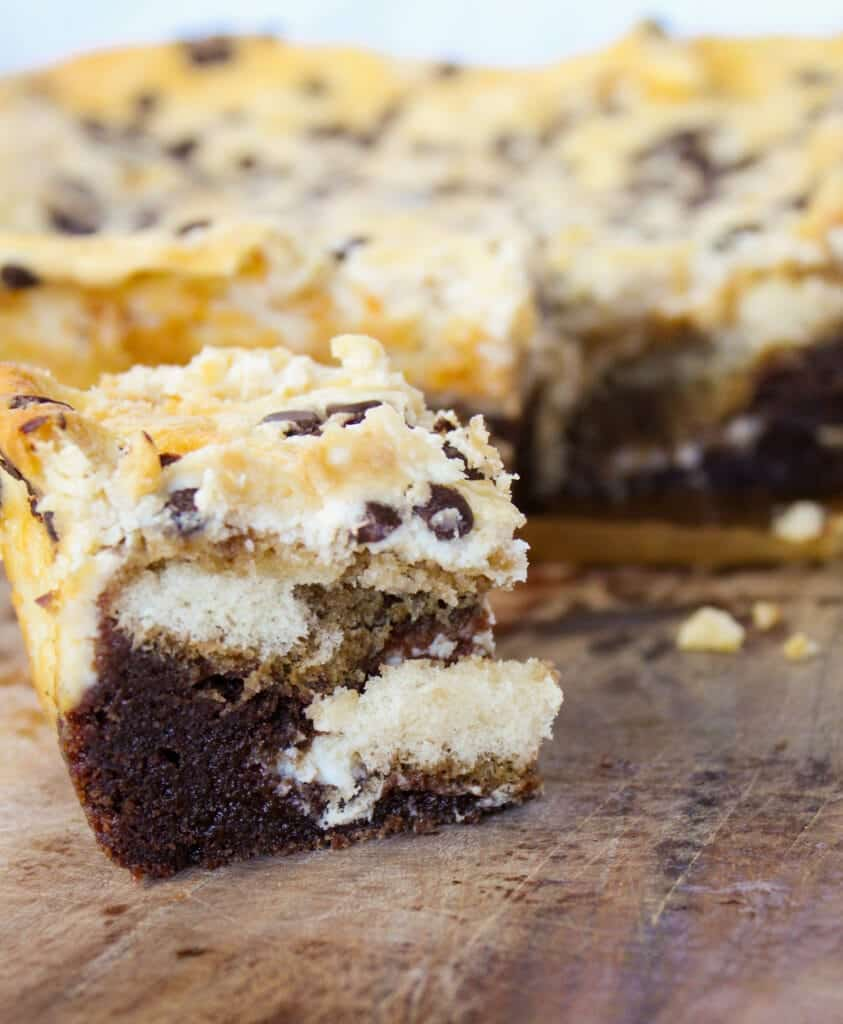close up shot of a piece of tiramisu cheesecake brownies on a cutting board