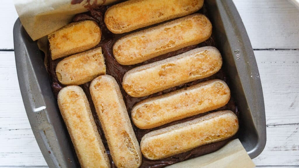 coffee soaked ladyfingers in a pan on top of brownie batter