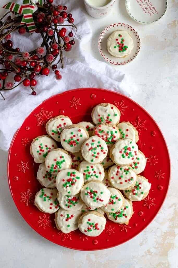 red plate with eggnog sugar cookies for christmas on them with red and green sprinkles
