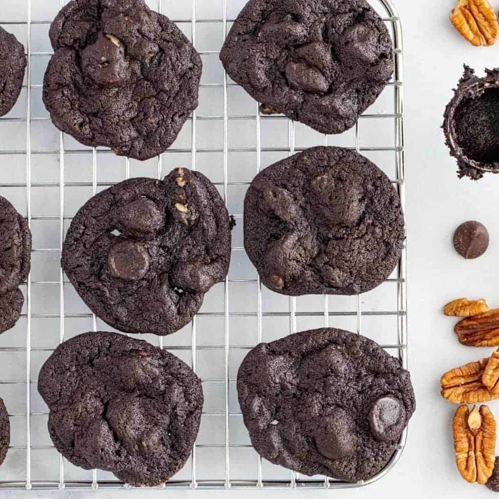 flourless chocolate cookies on a cooling rack with chopped pecans next to it