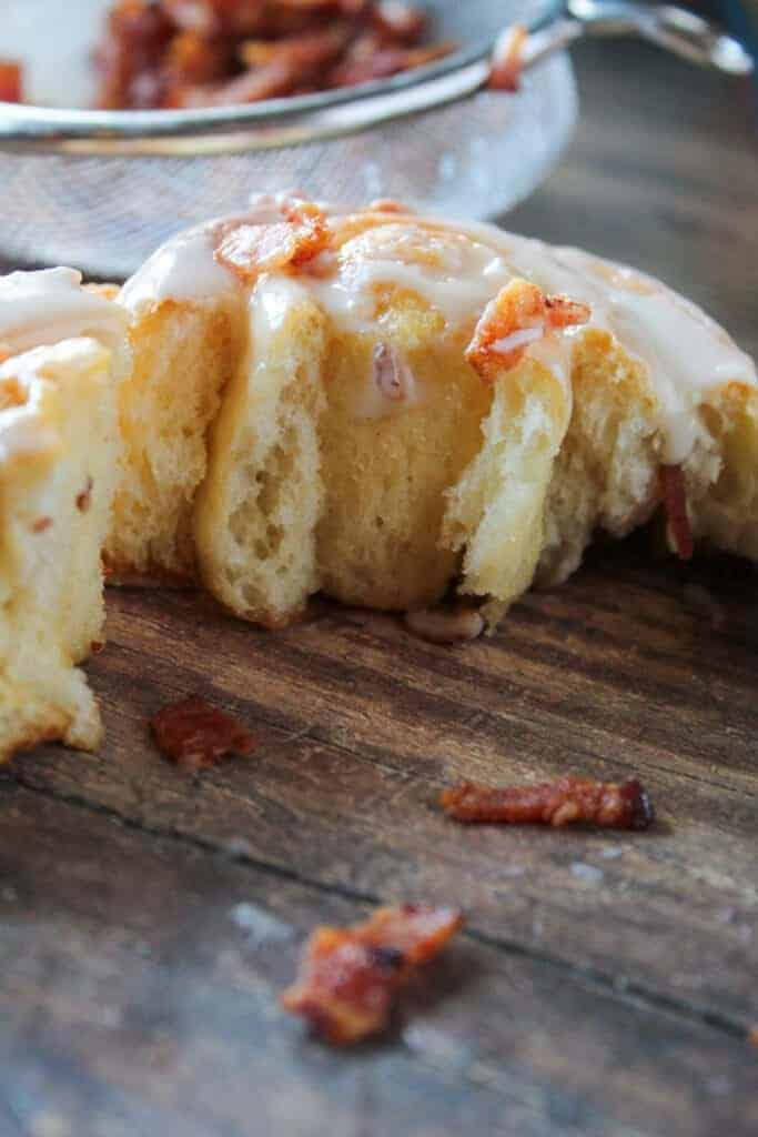 close up side shot of the inside of a maple and bacon sweet roll with diced cooked bacon pieces around it