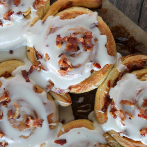 overhead shot of maple and bacon sweet rolls on parchment paper