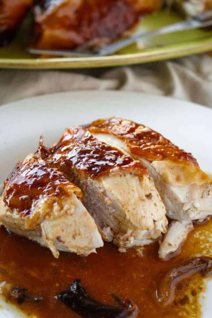 side view of a sliced turkey breast on a white plate with gravy with thanksgiving roast turkey in the background