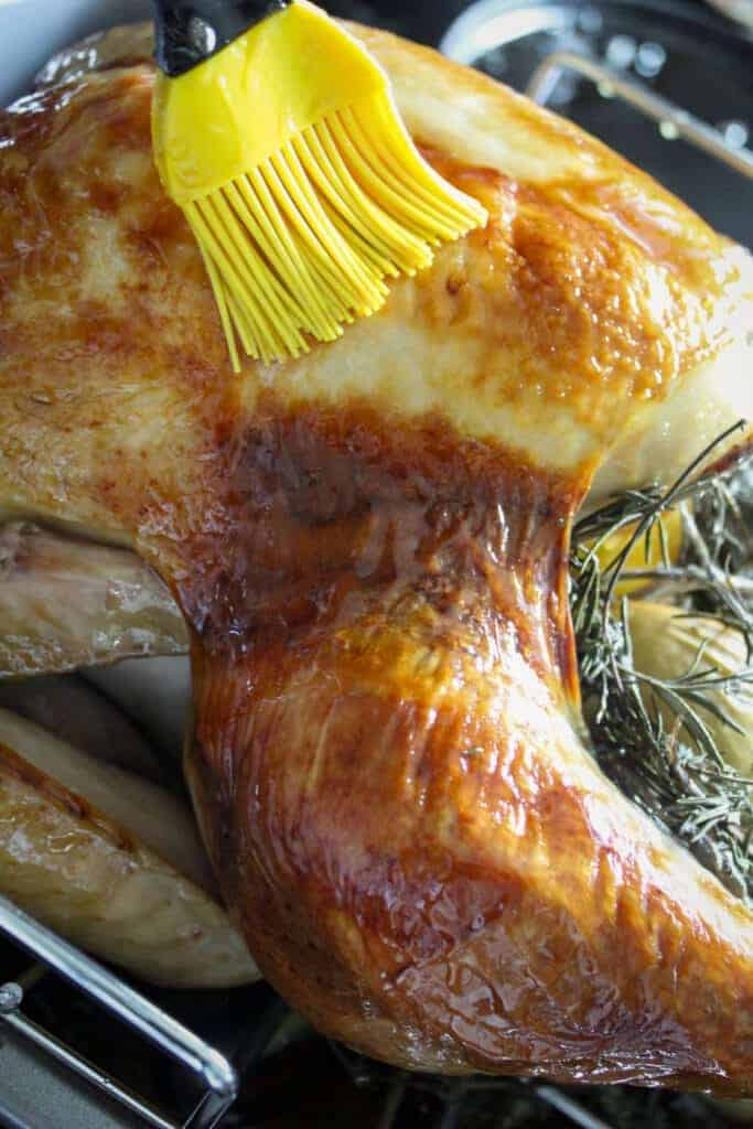 yellow basting brush spreading maple glaze over a whole turkey in a roasting pan
